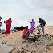 A family outside their tent as breakfast is being prepared at at the Mbera camp for Malian refugees in Mauritania on 2 March 2013.