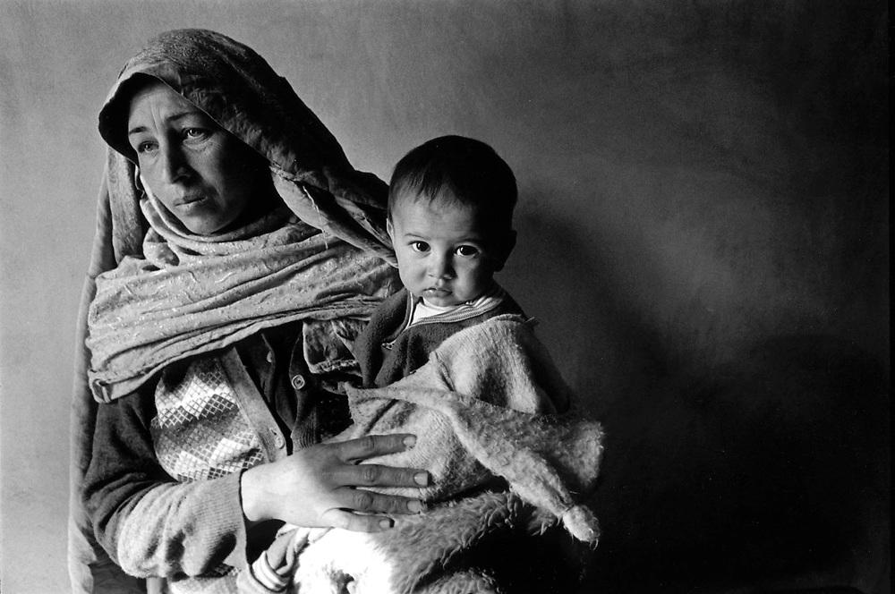 AFGHANISTAN 1996 - UNDER TALIBAN;HERE: Food distribution - Tajik woman with her child waiting for ration;Armut durch Taliban-Regime.Hier:Lebensmittelverteilung durch ACF (Action contre.le faime)  Tadschikische Frau mit ihrem Kind warten auf.die Zuteilung von Lebensmitteln.<br /> copyright: Christian Jungeblodt