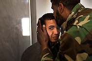 A rebel kisses a young man after he was stopped and questioned at a check poin in eastern Libya on March 1, 2011.
