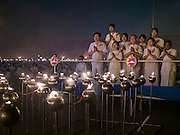 "22 FEBRUARY 2016 - KHLONG LUANG, PATHUM THANI, THAILAND:  A family prays after lighting lamps during the Makha Bucha Day service at Wat Phra Dhammakaya.  Makha Bucha Day is a public holiday in Cambodia, Laos, Myanmar and Thailand. Many people go to the temple to perform merit-making activities on Makha Bucha Day, which marks four important events in Buddhism: 1,250 disciples came to see the Buddha without being summoned, all of them were Arhantas, Enlightened Ones, and all were ordained by the Buddha himself. The Buddha gave those Arhantas the principles of Buddhism, called ""The ovadhapatimokha"". Those principles are:  1) To cease from all evil, 2) To do what is good, 3) To cleanse one's mind. The Buddha delivered an important sermon on that day which laid down the principles of the Buddhist teachings. In Thailand, this teaching has been dubbed the ""Heart of Buddhism."" Wat Phra Dhammakaya is the center of the Dhammakaya Movement, a Buddhist sect founded in the 1970s and led by Phra Dhammachayo.     PHOTO BY JACK KURTZ"