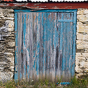 Old weathered blue door in stone house at Clyde, South Island, New Zealand.