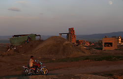 A picture made available on 05 July 2012 of a Mongolian motorcyclist riding past a coal mine in the mining town of Nalaikh in Mongolia, 02 July 2012. Once a thriving mining town, Nalaikh is one of first and oldest mining site in Mongolia but has seen a decline in its fortune as mining disasters and accidents plague the site. With little government oversight, only a handful of small companies and informal miners work on the site with scant regard to safety standards. Mongolia is rich in a variety of natural resources including forests, coal, iron ore, gold and copper. Expansion of the mining industry has turned the sector into the most important income source and led to an economic growth rate last year of around 17 per cent. The majority of raw materials are exported to China. Seeking to to reduce the dependency on China for exports and Russian imports, Mongolia has embarked on a policy of closer economic ties with other countries such as Germany, Canada and the United States. Despite impressive growth rates, about one-third of the population lives below the poverty line while unemployment and inflation are high.