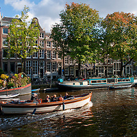 Amsterdam, Holland. Boat heading down a canal with the traditional Dutch buildings set back from the water.