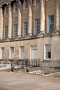 """The Royal Crescent is a residential road of 30 houses, laid out in a crescent, in the city of Bath, England. Designed by the architect John Wood the Younger and built between 1767 and 1774, it is among the greatest examples of Georgian architecture to be found in the United Kingdom and is a grade I listed building...Wood designed the great curved façade of what appears to be about 30 three storey houses with Ionic columns on a rusticated ground floor. The columns are 30 inches (76 cm) in diameter reaching 47 feet (14.3 m) and there are 114 in total, each with an entablature 5 feet (1.5 m) deep. The central house has two sets of coupled columns. Each purchaser bought a certain length of the façade, and then employed their own architect to build a house to their own specifications behind it; hence what appears to be two houses is sometimes one. This system of town planning is betrayed at the rear of the crescent: while the front is completely uniform and symmetrical, the rear is a mixture of differing roof heights, juxtapositions and fenestration. This """"Queen Anne fronts and Mary-Anne backs"""" architecture occurs repeatedly in Bath..It was originally called just The Crescent and the adjective Royal was added at the end of the 18th century after Prince Frederick, Duke of York and Albany had lived at numbers 1 and 16...The Royal Crescent is constructed from Bath Stone is a Limestone comprising granular fragments of calcium carbonate its warm, honey colouring gives the  circus and much of Bath its distinctive appearance...VIEW MORE IMAGES of Royal Crescent, Bath, England, by Architect John Wood the Younger here"""