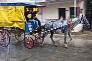 Coche de caballos in Holguin, Cuba in a heavy rain.