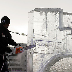 London, UK - 11 January 2012: a sculpture carves a block of ice with a chainsaw during the Ice sculpting festival 2013 in Canary Warf.