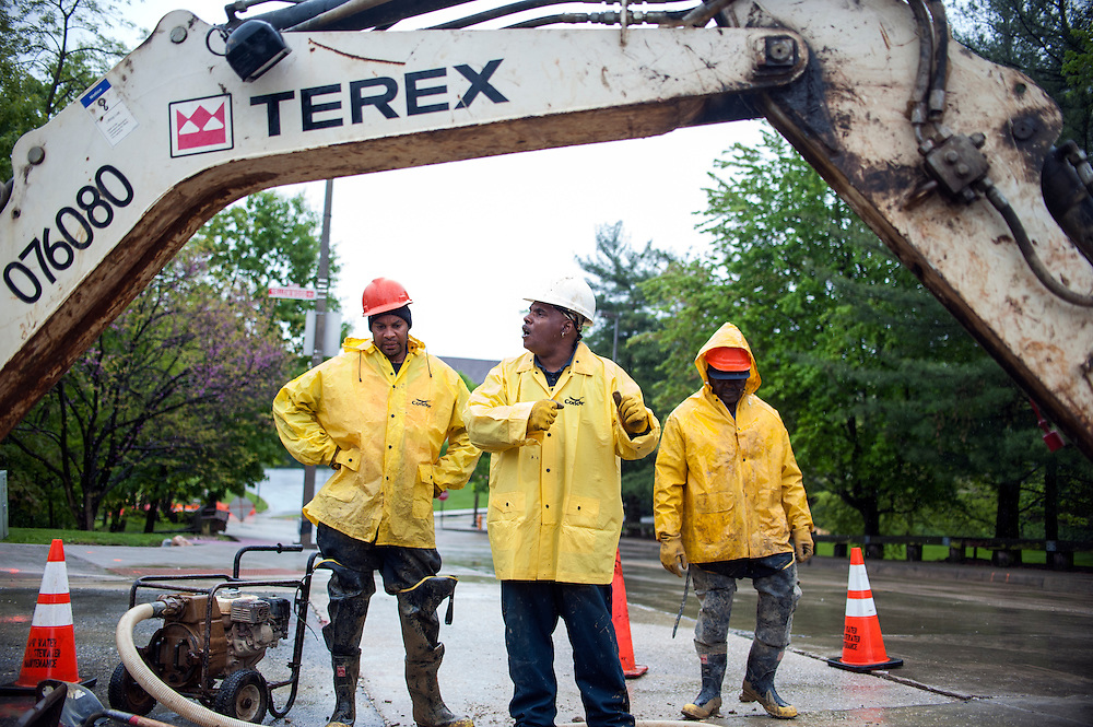 Photo by Matt Roth<br /> <br /> Baltimore City Department of Public Works employees (L-R) laborer William Spraggins, supervisor Chester Green, and utility repair II Edward Woolfolk, respond to a water main break at the intersection of Yellowwood Ave. and Springfield Dr. in Baltimore, Maryland on Tuesday, May 07, 2013.