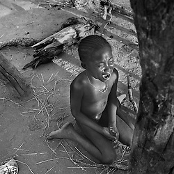 Awa Balde, who had been circumcised, cries after she has been hit by an elder sister.  The two months after the girls are circumcised are considered a time for discipline and learning the rules of becoming a woman.