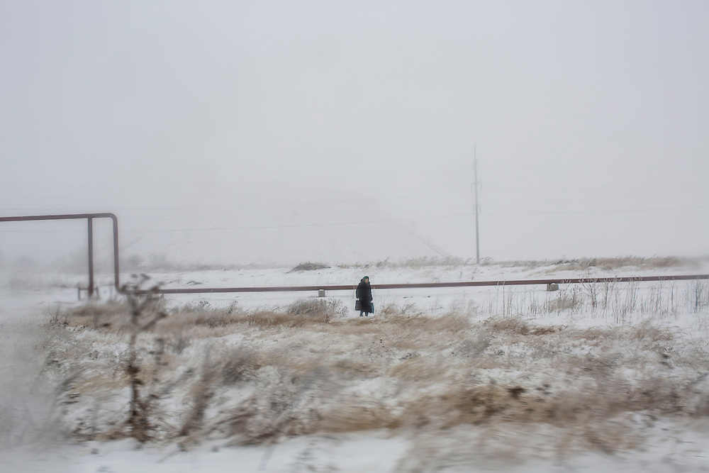 YURIVKA, UKRAINE - DECEMBER 8, 2014: A woman walks along the road near Yurivka, Ukraine. CREDIT: Brendan Hoffman for The New York Times