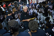 Aliquippa head coach Mike Zmijanac gives a final pep talk to his team before their homecoming game.<br /> <br /> Zmijanac has never played a down of organized football but he is the winningest coach of what is said to be the best high school program in the region. <br /> <br /> Due to the obstacles of violence and drugs in Aliquippa, Zmijanac says that he loses six or so of his players to the pull of the street each year. And although he will not hesitate to suspend a star player, he maintains an open-door policy if they want to come back, believing that everyone deserves a second chance and that he can't give up on them.<br /> <br /> The school has one of the smallest enrollments in the Western Pennsylvania Interscholastic Athletic League (WPIAL) with the class of 2013 having only 58 kids, including 28 boys.<br /> <br /> Technically, they could play against Class A completion but they elect to play at the AA level.<br /> <br /> Pretty steep obstacles for a coach and team to overcome, but the team averaged 10 wins a year for the past 30 years. Last year Aliquippa played in its 25th WPIAL championship game, the most of any school in the district and they have won a record 15 titles. 2014 was the seventh year in a row that the Quips were in the final, also a record.<br /> <br /> The team was the training ground to NFL greats like Mike Ditka, Sean Gilbert, and Ty Law, all of whom were Aliquippa graduates.