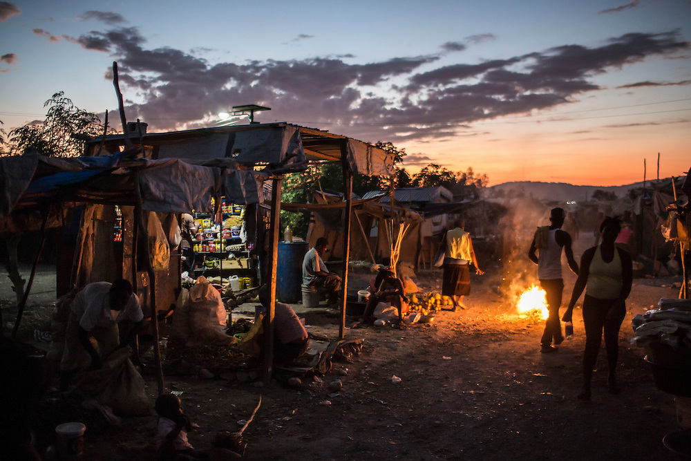 A street market at sunset at the Corail-Cesselesse camp for people displaced by the 2010 earthquake on Saturday, December 20, 2014 in Port-au-Prince, Haiti. The camp is home to tens of thousands of people, for most of whom there is no work or easy access to the center of town, some 18 kilometers away.