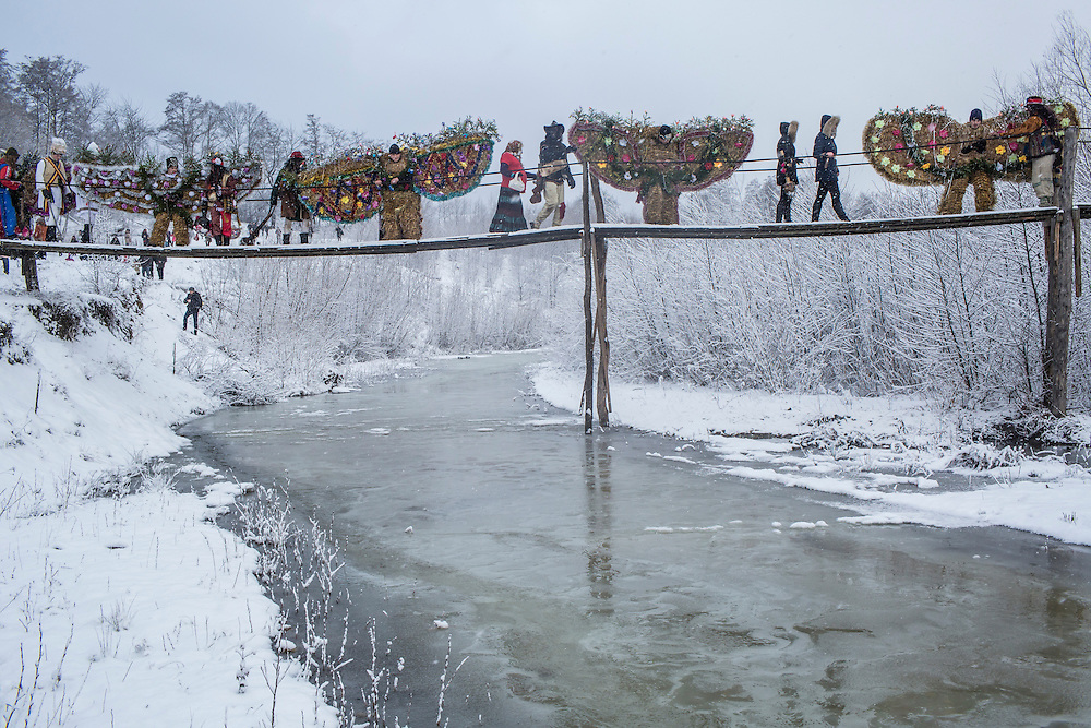 Revelers in costume cross a small footbridge during celebrations of the Malanka Festival on Thursday, January 14, 2016 in Krasnoilsk, Ukraine. The annual celebrations, which consist of costumed villagers going in a group from house to house singing, playing music, and performing skits, began the previous sundown, went all night, and will last until evening.