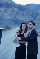 Dressed up couple in the Nevada Desert holding a road map looking to find the way out