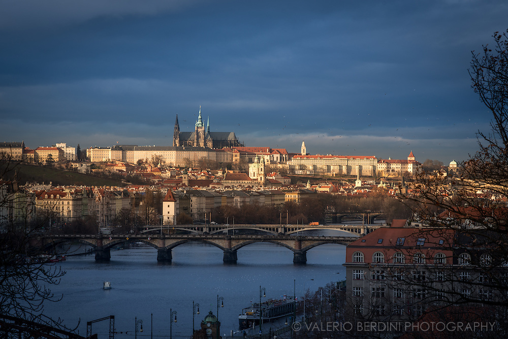 A sunray pierces the clouds and lit Prague Castle, seen from Saint Peter and Paul Basilica.