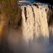 A vibrant rainbow forms in the mist of Snoqualmie Fall, Washington, during the spring melt. The water flow depicted here is about three times the annual average.