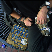 Nathan and his cat Fidget sit on the sidewalk outside of Pioneer Place at Fourth Ave. near the Max stop hoping for donations for food.