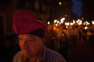A catalan wears the traditional hat, the barretina. Torchlight march on the eve of National Day (Diada). Every year the people of Catalonia celebrates the Independence Day on 11th September, when Catalonia troops where defeated by the army of Spain at the Siege of Barcelona in 1714. 300 hundreds years later, in 2013, Catalonian people commemorates this date protesting peacefully and claiming the independence with a human chain, called the Via Catalana, of around 400.000 persons, spreaded 400km along the whole catalonian land.