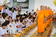 19 JULY 2014 - KHLONG LUANG, PATHUM THANI, THAILAND: Newly ordained monks and novices file into the canteen for lunch after their ordination at Wat Phra Dhammakaya. Seventy-seven men from 18 countries were ordained as Buddhist monks and novices at Wat Phra Dhammakaya, a Buddhist temple  north of Bangkok, Saturday. It is the center of the Dhammakaya Movement, a Buddhist sect founded in the 1970s and led by Phra Dhammachayo (Phrathepyanmahamuni). It is the largest temple in Thailand. The Dhammakaya sect has an active outreach program that attracts visitors from around the world.    PHOTO BY JACK KURTZ