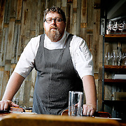 SHOT 8/15/13 4:12:36 PM - Justin Brunson, Owner and Executive Chef at Old Major, poses for a portrait in the main dining room at the restaurant in Denver, Co.  The restaurant focuses on heritage-raised meats from Colorado farms, features an in-house butchery program and bills itself as contemporary farmhouse cuisine. (Photo by Marc Piscotty / © 2013)