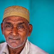 A Tamil Muslim man. A you portrait on a blue wall.