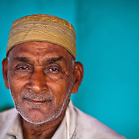 A Tamil Muslim man. A you portrait on a blue wall.