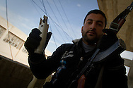 A Free Syrian Army soldier shows the remains of a morter fired into the city from government forces inside a school. Al Janoudiyah, Syria