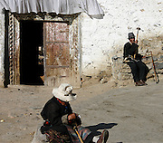 local tibetans resting near a monastery entrance in lhasa tibet