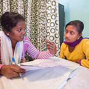 CAPTION: This is the Adolescent Reproductive and Sexual Health (ARSH) clinic at Ghatshila Community Health Centre (CHC). Atosi Shit (right) is an adolescent client, and Sarita Kumari Panna (left) is an ARSH Counselor. Here, Kumari is giving information on hygienic practices during the menstrual cycle in order to guard against infection and possible infertility. The ARSH clinics have been designed to provide health-related services to young people aged between 10 and 19 at a time when they are going through a lot of changes, both physically and mentally. This can mean anything from getting a small wound dressed to getting an abortion. LOCATION: Adolescent Reproductive and Sexual Health (ARSH) clinic, Ghatshila Community Health Centre (CHC), Purbi Singhbhum (district), Jharkhand (state), India. INDIVIDUAL(S) PHOTOGRAPHED: Sarita Kumari Panna (left) and Atosi Shit (right).