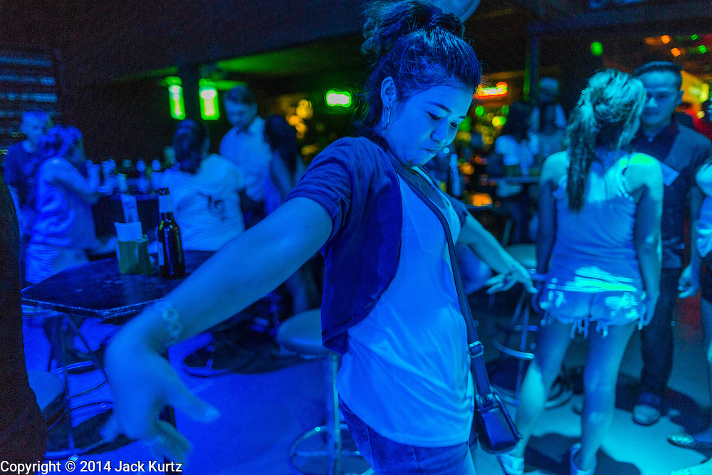 """26 SEPTEMBER 2014 - PATTAYA, CHONBURI, THAILAND: Women dance in a local bar that caters to mostly Thais in Pataya. Pataya, a beach resort about two hours from Bangkok, has wrestled with a reputation of having a high crime rate and being a haven for sex tourism. After the coup in May, the military government cracked down on other Thai beach resorts, notably Phuket and Hua Hin, putting military officers in charge of law enforcement and cleaning up unlicensed businesses that encroached on beaches. Pattaya city officials have launched their own crackdown and clean up in order to prevent a military crackdown. City officials have vowed to remake Pattaya as a """"family friendly"""" destination. City police and tourist police now patrol """"Walking Street,"""" Pattaya's notorious red light district, and officials are cracking down on unlicensed businesses on the beach.     PHOTO BY JACK KURTZ"""