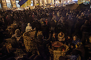 Anti government protesters warm themselves as they stands guard on one of the barricades surrounding Maidan square that is occupied by the protesters. Thousands of people have been protesting against the government since a decision by Ukrainian president Viktor Yanukovych to suspend a trade and partnership agreement with the European Union in favor of incentives from Russia. 14 December 2013.