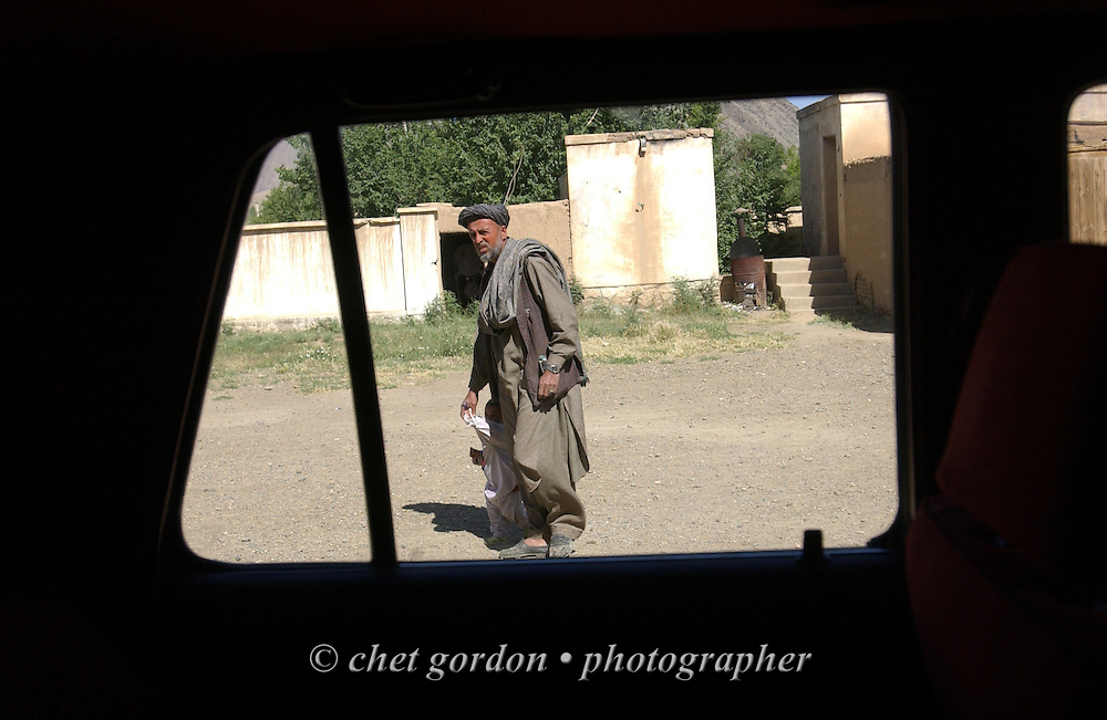 """An Afghan man seen through the window of a car at the Charasyab health clinic approximately 20 kilometers outside of Kabul, Afghanistan on Sunday, May 26, 2002. A humanitarian mission organized by The Geshundheit Instititute, founded by Dr. Hunter """"Patch"""" Adams, Lufthansa Cargo, and DHL Worldwide Express collaborated to ship medicines, food and orthopedic supplies to the Indira Ghandi Children's Hospital, clinics and orphanages in Kabul. The German NGO (Non Governmental Organization) Hammer Forum supervised the distribution of the donated supplies from various non-profit organizations in the U.S. and The Netherlands."""