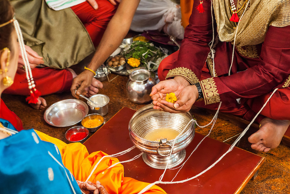 The groom at an Indian / Hindu wedding holding a flower above a silver bowl.