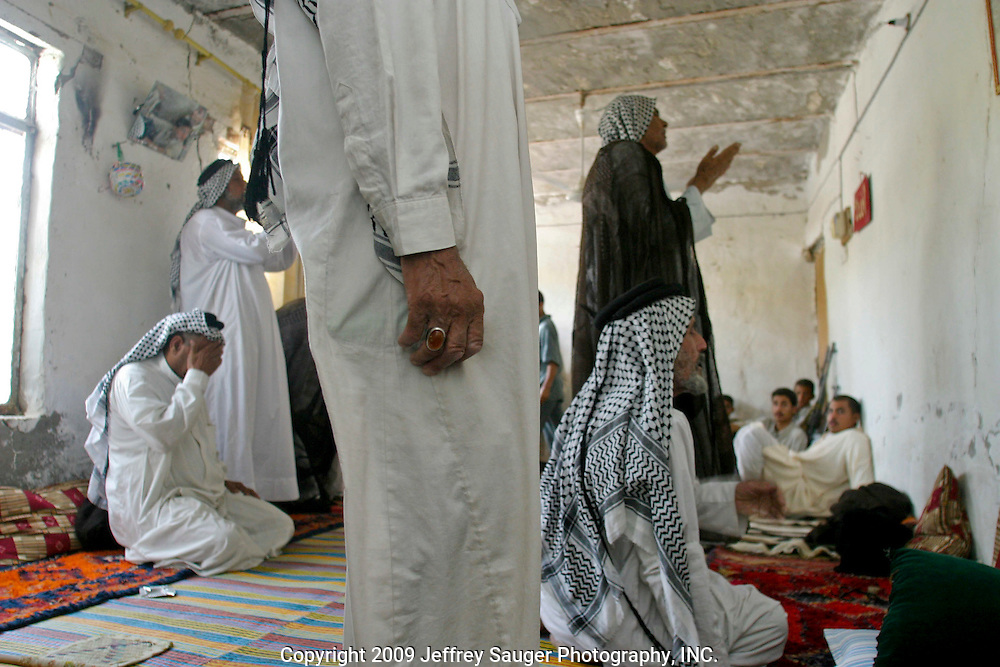 Members of the extended Al-kasid family and neighboring tribes pray before eating lunch at the family's Istikbal, or homecoming, in his home village Suq ash Shuyukh, about 20 miles southeast of Nasiriyah, Iraq, Tuesday, July 29, 2003. ..The Al-kasid family fled Iraq after the Gulf War and their part in the uprising against Saddam Hussein in 1991, spent 3 years in Rafa, Saudi Arabia and finally settled in Dearborn, MI. The family hasn't been home to Iraq in 13 years.