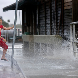 Carli Marie Kocjancic plays in the surge generated by Tropical Storm Alberto as the waves break onto a road in Cedar Key, Florida June 13, 2006. REUTERS/Scott Audette