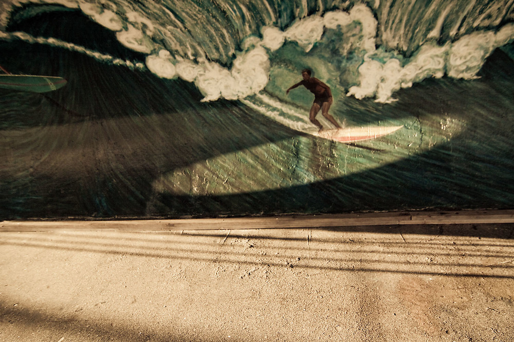 Light through a nearby portal mimics a surfboard on a mural on a surfing mural in Rockaway Beach, Queens, NY.