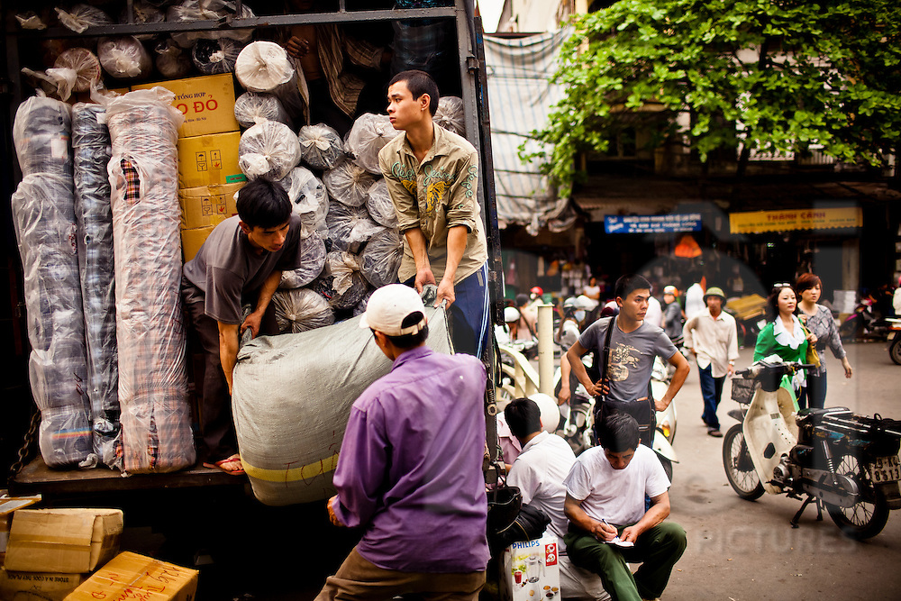 Young men unload a truck of fabrics and other goods at Dong Xuan Market in Hanoi, Vietnam. Dong Xuan is one of the capital's largest markets.