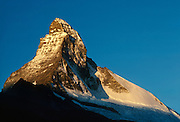 """The Matterhorn (4478 meters or 14,980 feet, Monte Cervino in Italian, Mont Cervin in French) catches sunrise light, seen from Zermatt, Switzerland. Small electric taxis serve Zermatt, which bars combustion-engine cars to help preserve small village atmosphere and prevent air pollution. The famous mountaineering and ski resort of Zermatt lies at 1620 meters or 5310 feet elevation at the head of Mattertal (Matter Valley) in Valais canton, Switzerland, the Pennine Alps, Europe. The German word matten means """"alpine meadows."""" Most visitors reach Zermatt by cog railway train from the nearby town of Täsch (Zermatt shuttle). Trains also depart for Zermatt from farther down the valley at Visp and Brig on the main Swiss rail network. Hike the High Route (Chamonix-Zermatt Haute Route) for exceptional mountain scenery. Published in Wilderness Travel 1992 Catalog of Adventures. Published in """"Light Travel: Photography on the Go"""" book by Tom Dempsey 2009, 2010."""