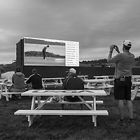 A few spectators remain in a viewing area as the second round fades into dusk.
