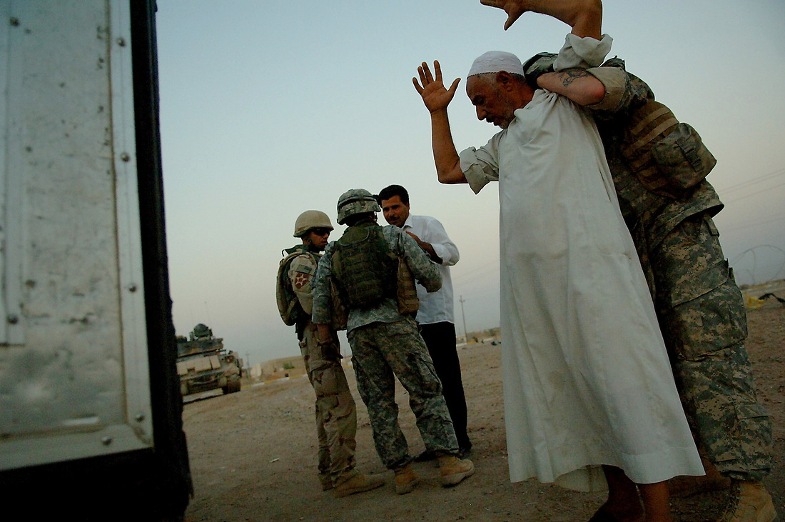Soldiers from Bravo Company, 2-6 Infantry, Task Force 1-35 Armored Division, Baumholder, Germany, search a couple of local Iraqi's on August 7, 2006 that didn't pull over during a Traffic Control Point (TCP) on Alternate Supply Route Michigan in Tameem, Iraq. TCP's are performed by pulling over random vehicles, searching the vehicle and it's occupants for weapons or explosives being transported into the city. — © TSgt Jeremy Lock/