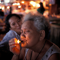 Philippines, Cebu Island, Woman smokes cigar inside Carbon Market along city's waterfront.