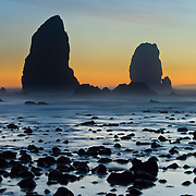 The pounding Pacific Ocean has eroded sea stack rocks from bluffs at Cannon Beach, Oregon, USA -- at dusk, the sky glows yellow orange. A time exposure blurs restless currents swirling at low tide.