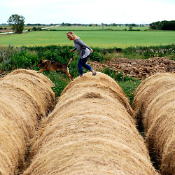 Melanie and Wylie leap the gaps between straw bales at her family's farm in Stony Mountain, Manitoba, Canada.