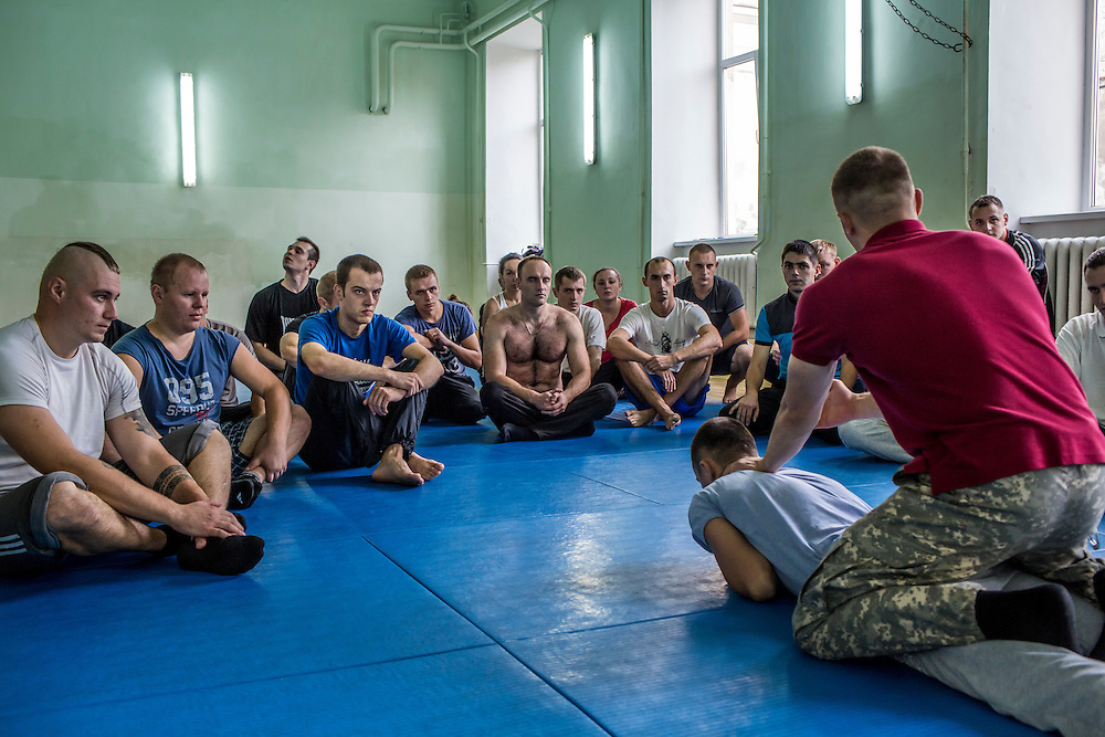 LVIV, UKRAINE - OCTOBER 5, 2015: Instructor Pavlo Besaga, in red, shows recruits how to subdue and handcuff a subject as part of tactical training for new patrol police officers in Lviv, Ukraine. In an effort to reform the notoriously corrupt Ukrainian police force, an entirely new force has been established in several cities, including Kiev and Lviv, with a primary focus on patrolling the streets. CREDIT: Brendan Hoffman for The New York Times