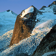 """Hound's Tooth and Bugaboo Glacier, Bugaboo Provincial Park, British Columbia, Canada. The Bugaboos are a range in the Purcell Mountains, which are a subrange of the Columbia Mountains, which are west of the Rocky Mountain Trench. (Some USA maps label the """"Percell Mountains"""" where their southern limit protrudes into the states of Idaho and Montana.) The igneous Bugaboo intrusion of 135 million years ago cooled into hard crystalline granite and was scraped into spires by glaciers eroding surrounding rock dating from 600 million to 1 billion years ago."""