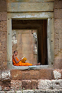 A young monk studies Buddhist teachings in the shade of a stone structure in the Angkor Wat temple complex of Siam Reap, Cambodia.