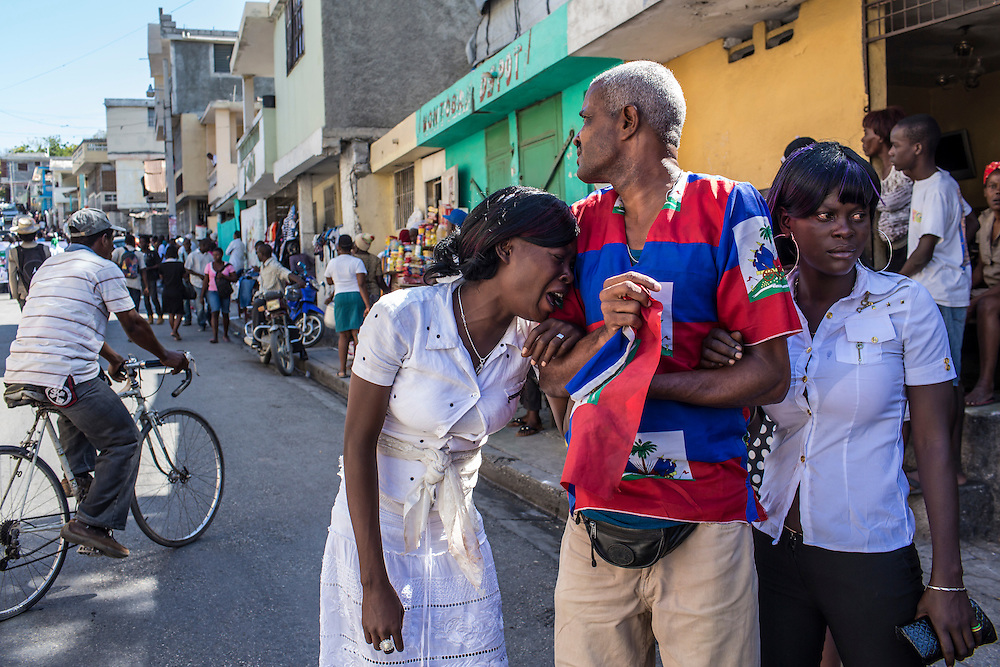 Bertha Nicolas, 20, left, and Betty Nicolas, 23, right, grieve at the funeral of their brother Jolin Nicolas, 19, on Monday, December 22, 2014 in Port-au-Prince, Haiti. Nicolas was killed by police while participating in anti-government protests on December 13, and many of the mourners came from political groups such as MOPOD, a block of opposition political parties, and Klere J'aie Ayiti that are aligned against President Michel Martelly