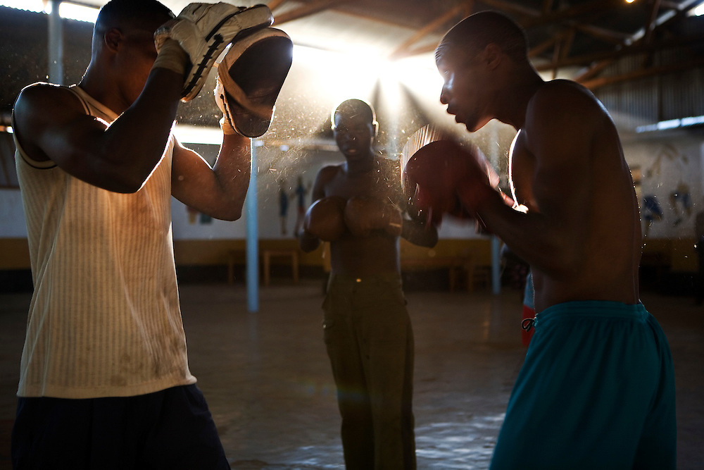 3 young men practicing boxing during a late afternoon training session at their community centre in Iringa, Tanzania.