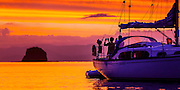 Two friends photographing an intense sunset from the cockpit of their yacht Muritai, while at anchor in Parapara Bay, Great Mercury Island, New Zealand.