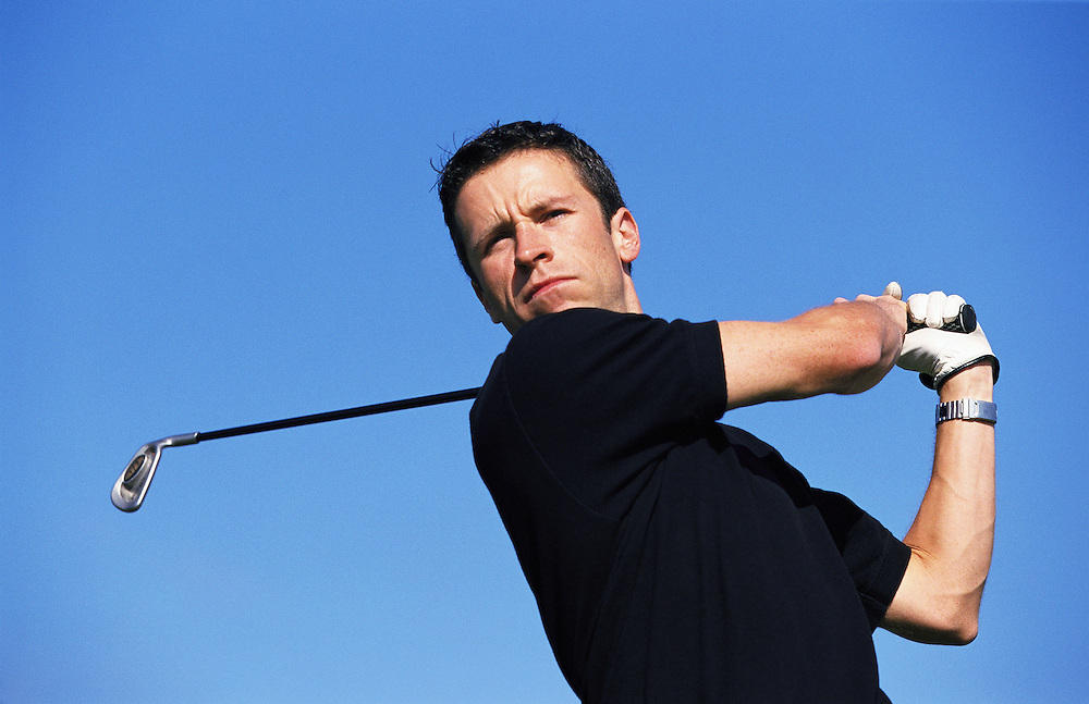 Early 30's Caucasian man watching his golf ball on the follow through of a tee shot.<br />