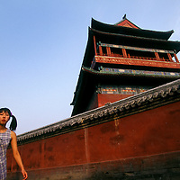 Young woman walking along a hutong behind the historic Drum Tower at the end of summer.<br /> <br /> From China [sur]real &not;&copy; Mark Henley